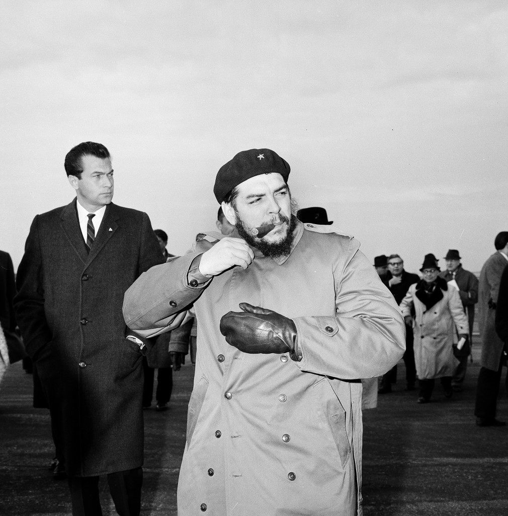 "Cuba's Minister of Industry, Ernesto ""Che"" Guevara, buttons his coat at New York's Kennedy Airport, Dec. 17, 1964, prior to taking off for an unexplained flight to Gander, Newfoundland. (AP Photo)"
