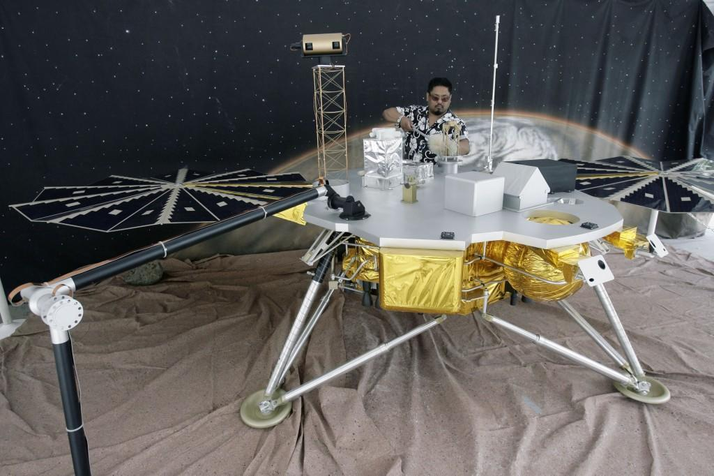 JoJo Aguilar, a Mars exploration team member, dusts a full-scale model of the Phoenix lander Thursday, May 22, 2008, at NASA's Jet Propulsion Laboratory in Pasadena, Calif. The lander will reach Mars on Sunday, May 25, to begin a three-month mission studying an arctic site on the Red Planet. (AP Photo/Ric Francis)