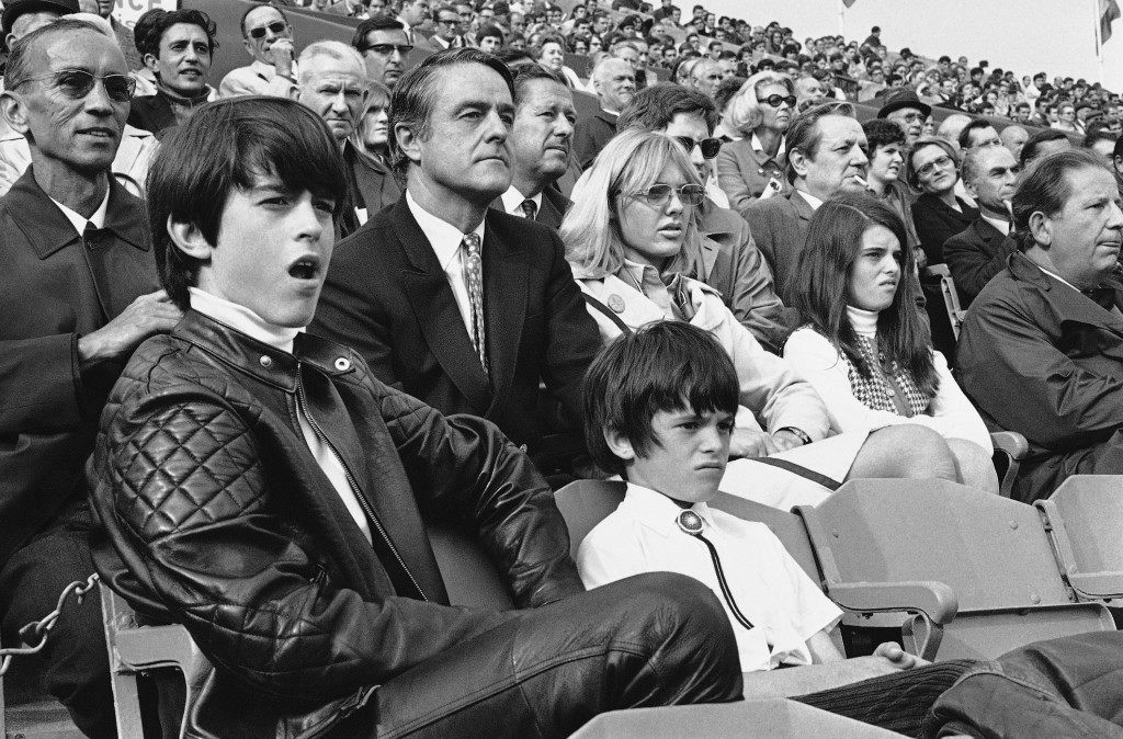 U.S. Ambassador to France Sargent Shriver watches a match in the French international tennis championships at Roland Garros stadium in Paris on May 31, 1969. Stated around him are, Carol Osche, a friend, wearing classes, daughter Maria, right; and sons Robert, left, and Timothy, center foreground. (AP Photo)