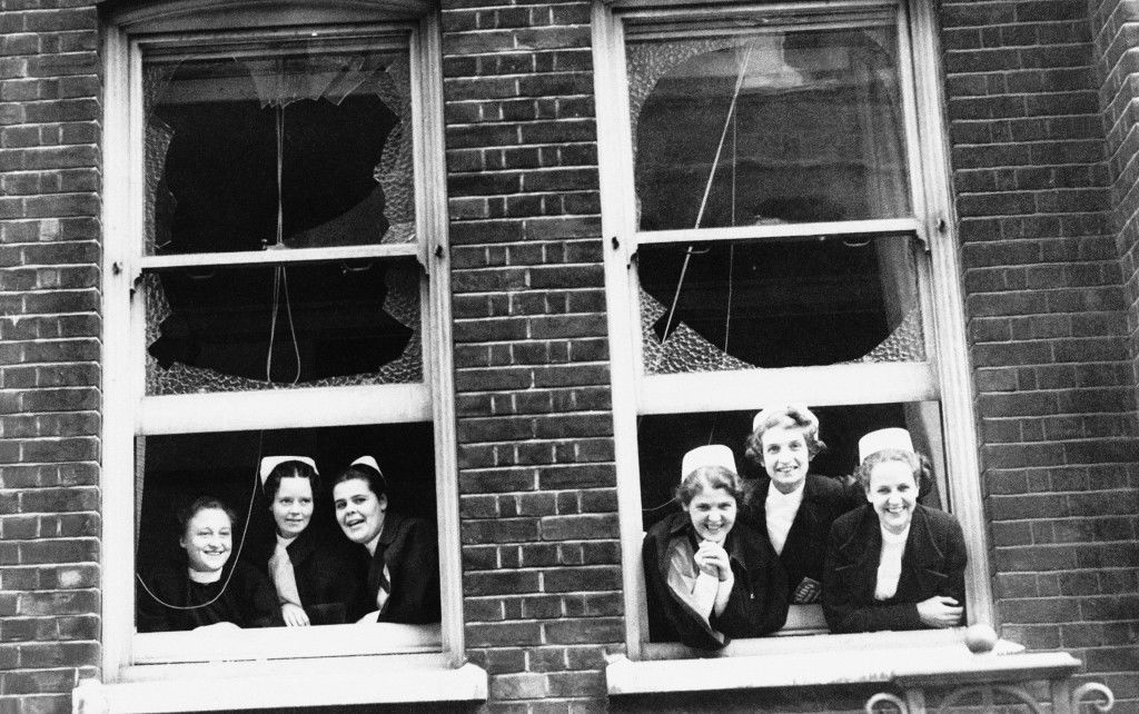 A row of smiling faces nurses, calm and cheerful; look out, Sept. 9, 1940 in London. Through the broken windows of their damaged home a high explosive bomb fell on their East London Hospital last night but all were safe in their shelter and there were no casualties. (AP Photo)
