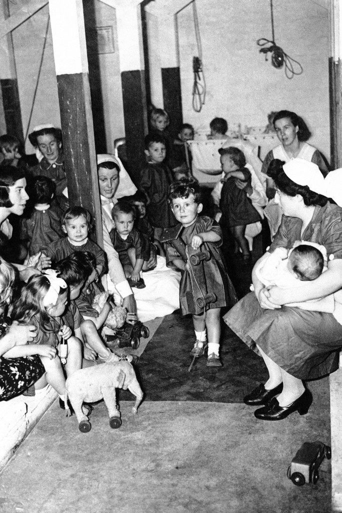 Pancras day nursery for has an A.R.P. bomb-proof nursery tom in London, August 2, 1940 to which the children are trooped daily, singing ?now we go down the steps again? and thinking it a royal game. (AP Photo)