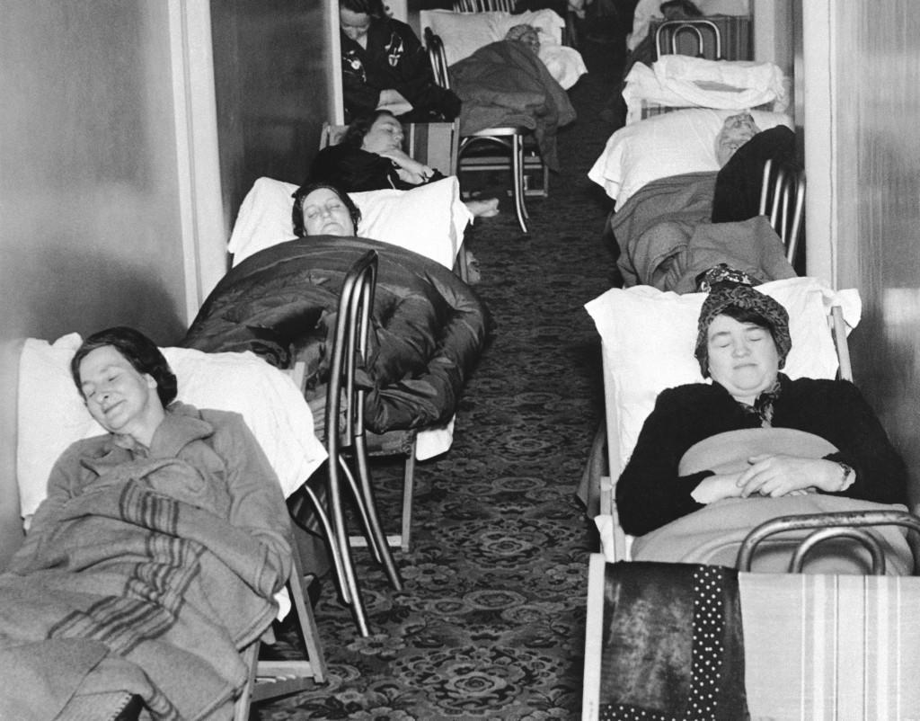 Women sleep in a corridor of the Grosvenor house hotel in London, Dec. 17, 1940, their bodies stretched over chairs and deck chairs.
