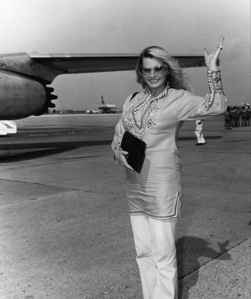 Swedish actress Anita Ekberg waves goodbye to friends before boarding a plane at Rome's Fiumicino airport on Oct. 1, 1970. Ekberg is en route to Seoul, Korea, to star in a new film being shot on location there. (AP Photo)