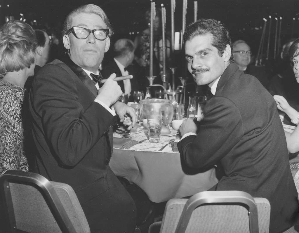 Co-stars Peter O'Toole, smoking a cigar, and Omar Sharif sit together at a dinner party following the movie premiere. Ref #: PA.8646692  Date: 21/12/1962