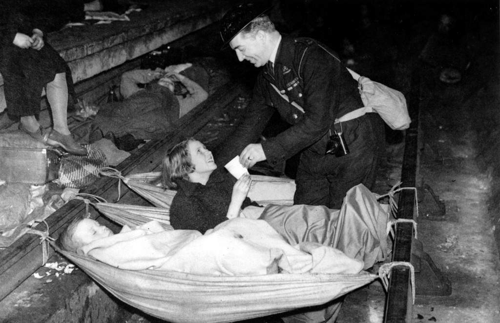 An air raid warden brings a drink of water for a young girl who has awakened during the night in an air raid shelter at the Aldwych tube station in London, England, Oct. 21, 1940 during the blitz in World War II. Hammocks are slung across the train tracks for sleeping. (AP Photo)
