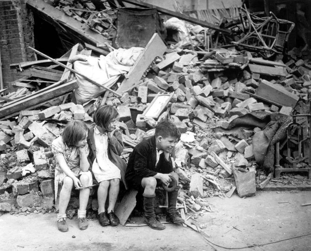 After another night of German bombings in September 1940, three children are sitting next to the remains of what was once their home in East London, in the early days of the Blitz during World War II. (AP Photo)