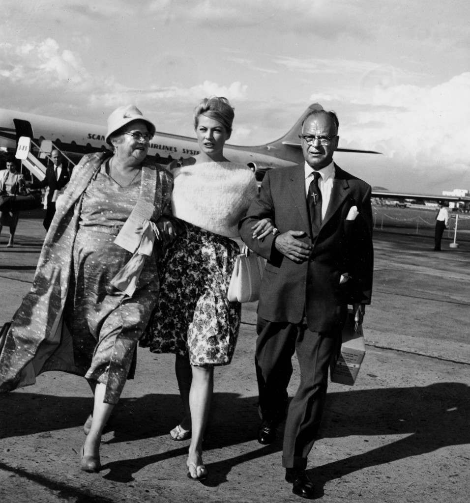 PA. 8691578 Swedish-born actress Anita Ekberg links arms with her mother and father after they arrive from Sweden at Rome's Ciampino airfield Sept. 3, 1959. (AP Photo/Porry Pastorel)