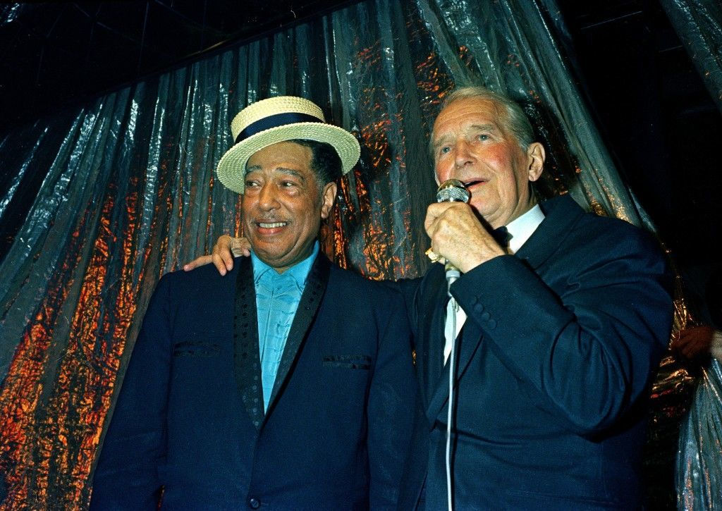 American orchestra leader Duke Ellington wears a straw hat presented by French singer Maurice Chevalier during the 70th birthday party for Ellington in Paris, France, in 1969. Ellington's birthday is April 29. (AP Photo)