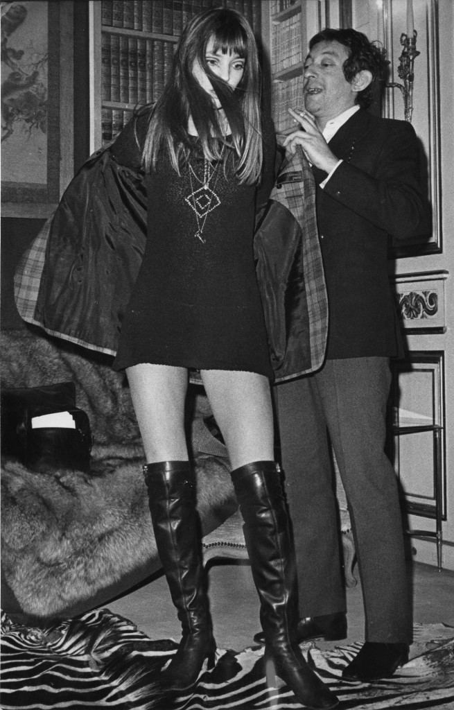 French singer and composer Serge Gainsbourg helps his wife, British actress and singer Jane Birkin, take off her coat in Paris, France.