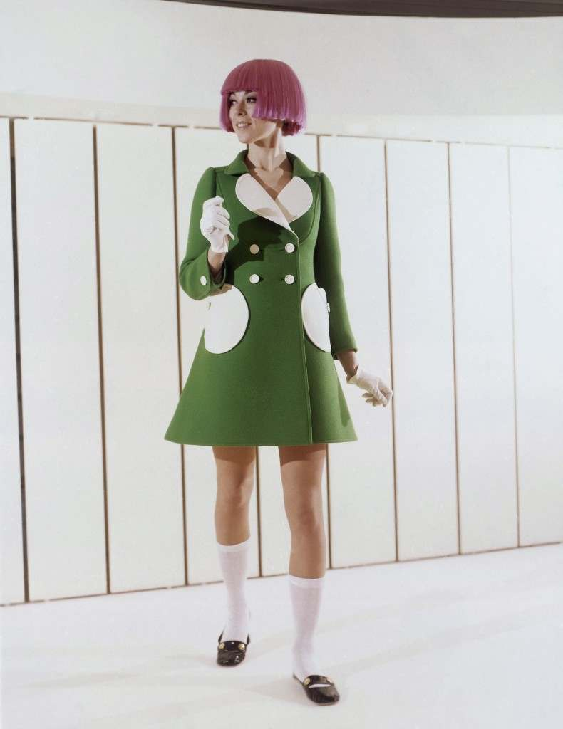 Green woolen coat with round pockets and white reverse was shown by the Andre Courages fashion house during the Paris Spring and Summer showings in 1969. Buttons are white and the wears a bright colored wig, White cotton socks and black leather flat holed shoes. (AP Photo)