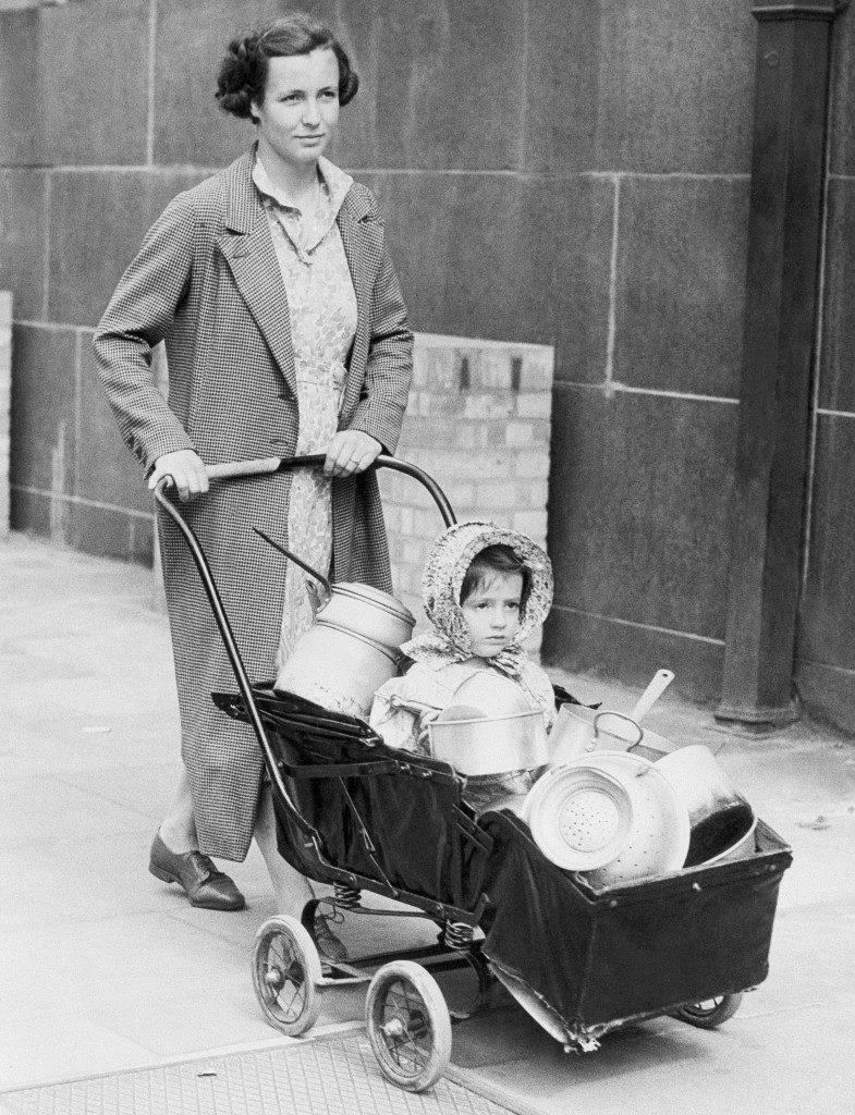 A housewife and her baby rings her contribution of pots and pans to Chelsea Town Hall, London, Oct. 7, 1940 after Lord Beaverbrook made an appeal to the women of Britain to give their aluminum pot and pans to be convert to into spitfires and hurricanes. (AP Photo)