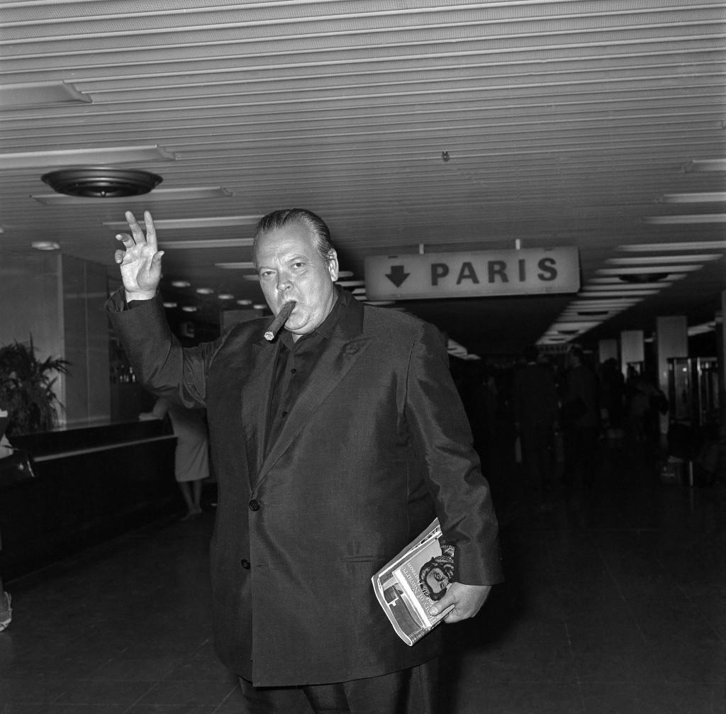 "With a Winston Churchill-size cigar, American film director Orson Welles arrives at Orly Airport, July 19, 1966 from Madrid. He will attend the Paris premiere of his film ""Shimes at Midnight"" adapted from Shakespeare's ""Falstaff"" and fly back to Madrid on July 20, to resume work on his latest film ""Don Quixotte"". (AP Photo/Levy)"