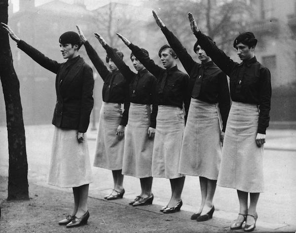 Women 'black-shirts' giving the fascist salute. Their uniform is a black shirt and tie, beret and slightly flared grey skirts.