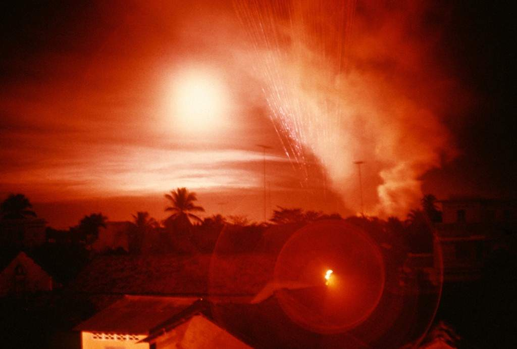 Tet Offensive, Saigon. Overhead a helicopter gunship fires 5,000 bullets a minute. Every Every fifth bullet is a red tracer that helps direct fire to its target.Vietnam, February 1968