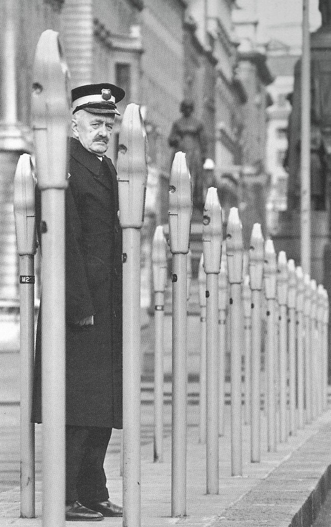 This is 1960 and a Metropolitan Police Traffic Warden poses amongst a forest of newly installed parking meters in Waterloo Place. Spotter: Leonard Bentley