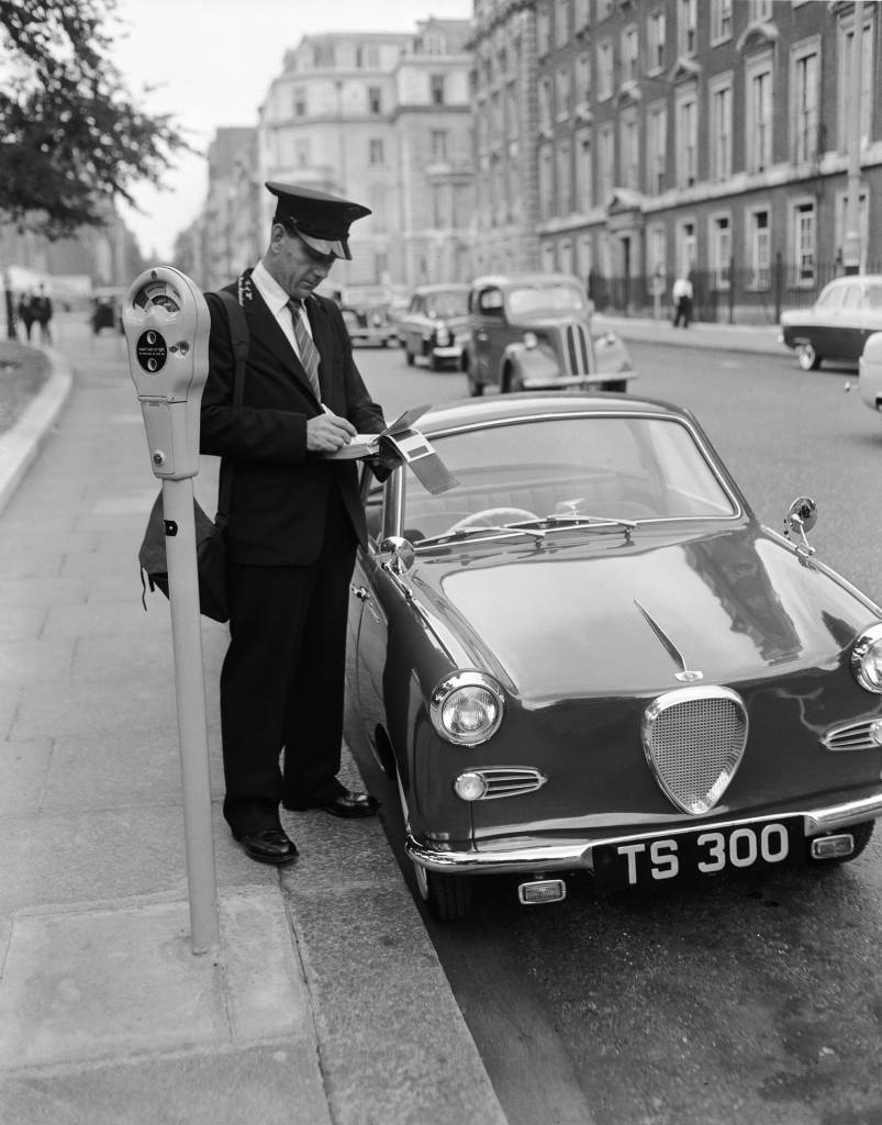 A traffic warden writing out a ticket for a car which had not paid the parking fee on the parking meter scheme in Mayfair, London. (Photo by Reg Birkett/Getty Images)