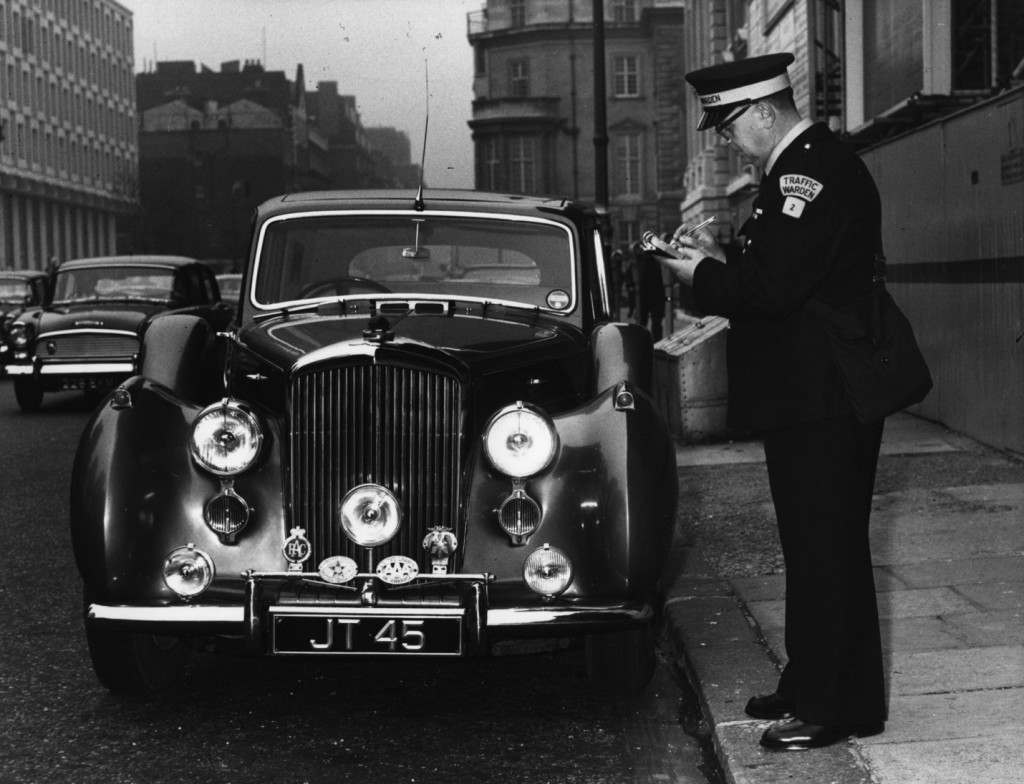 September 1960: A traffic warden writing a parking ticket in Grosvenor Square, London. Photograph: Hulton Archive/Getty Images