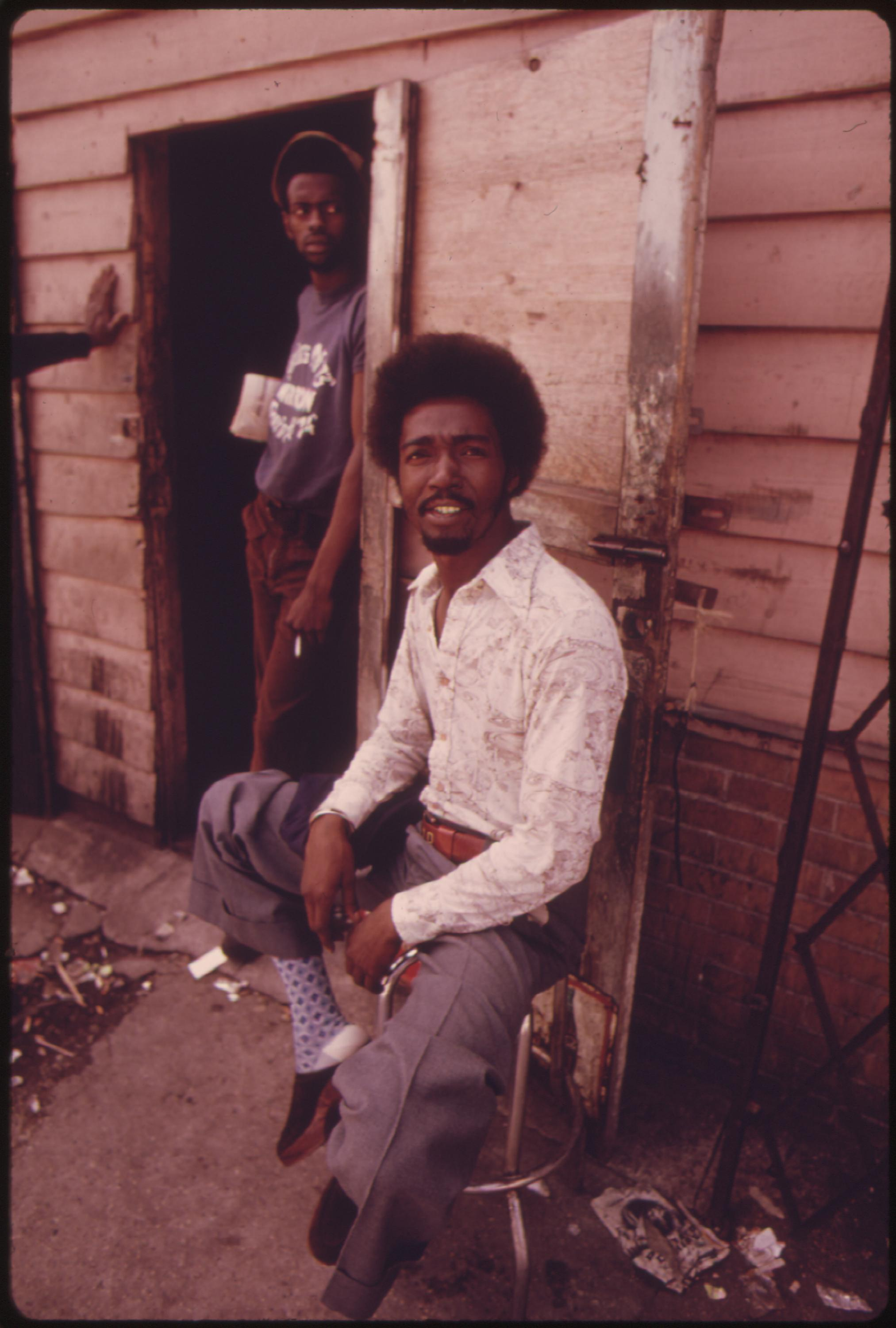 06:1973  Original Caption: Black Men At The Entrance To A Pool Hall Where They Hang Around Daily, Located On Roosevelt Road In The Heart Of The Ghetto On Chicago's West Side. John H. White