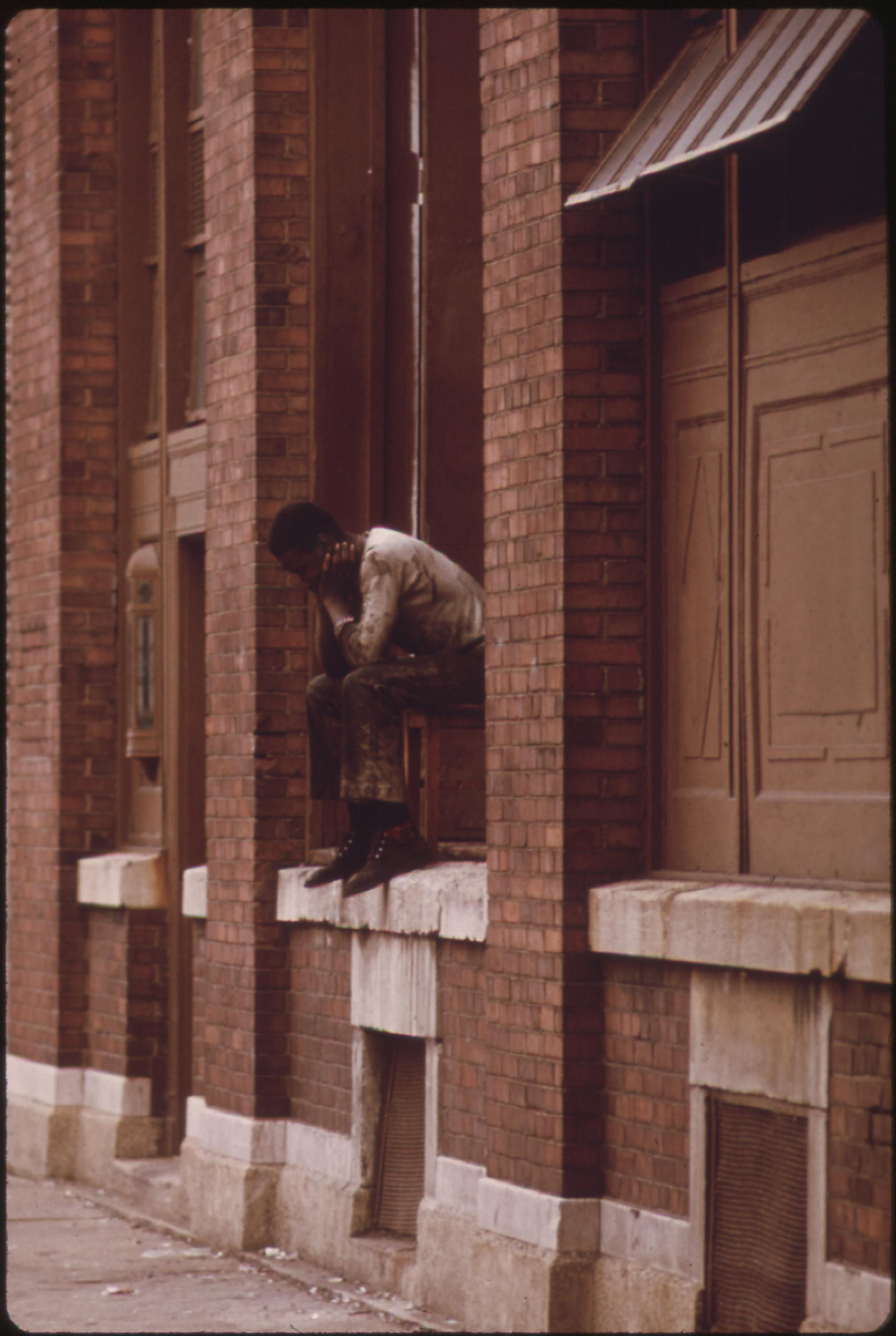 07:1973  Original Caption: A Black Man Who is Jobless Sits on the Windowsill of a Building in a High Crime Area on Chicago's South Side, He Has Nothing to Do and Nowhere to Go John H. White