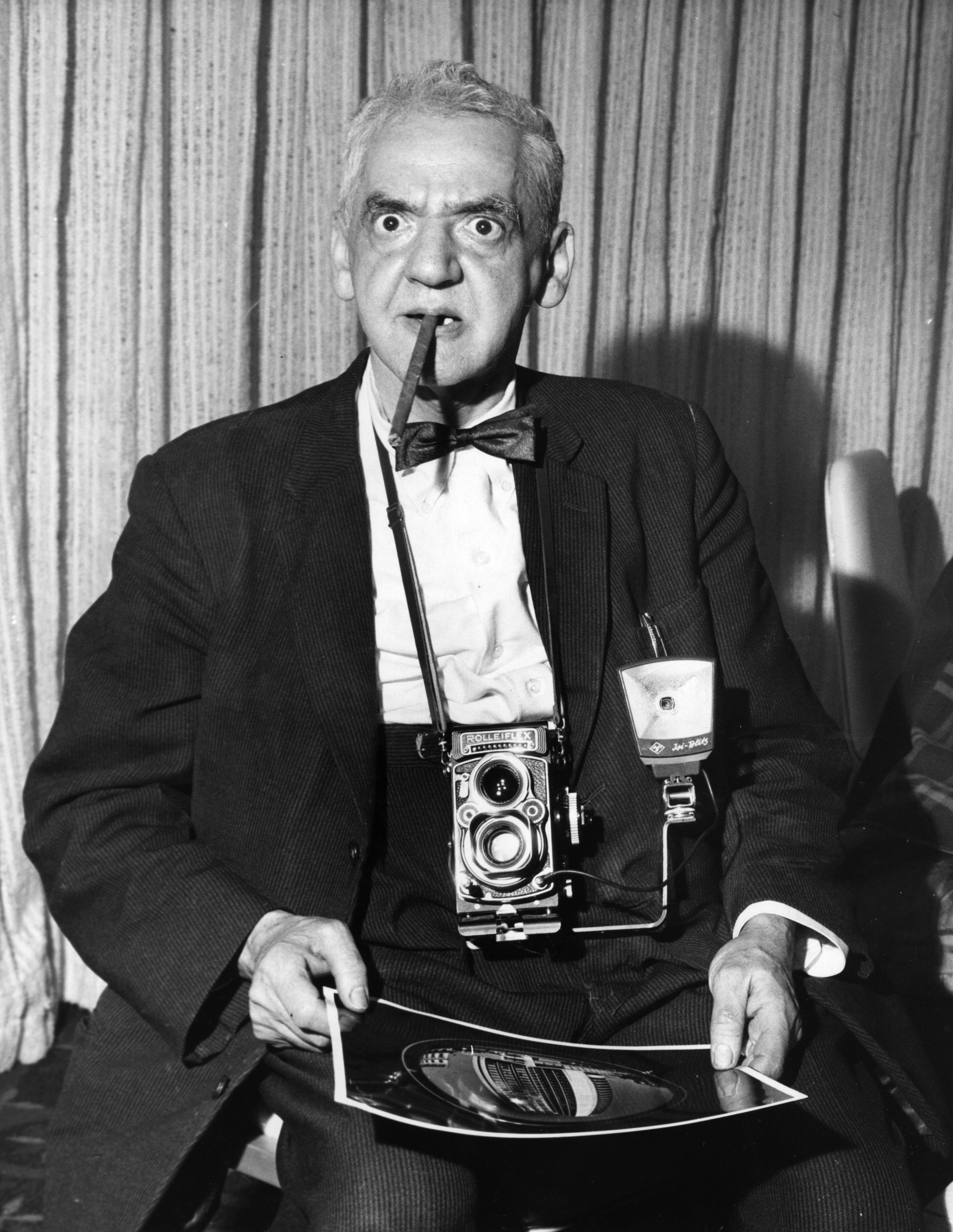 American photographer Weegee (1899 - 1969) with a photograph he took of the newly opened London Hilton Hotel, alongside Hyde Park.