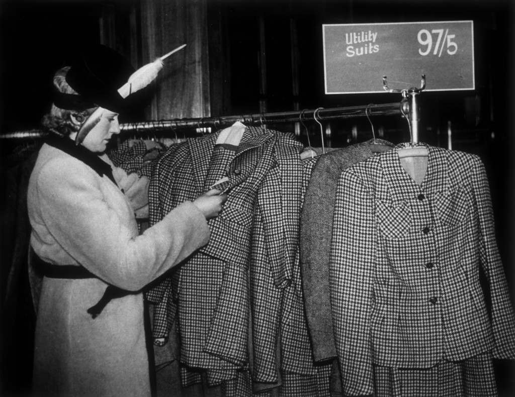 A woman looks at a collection of utility suits at a London store.   (Photo by Fox Photos/Getty Images)