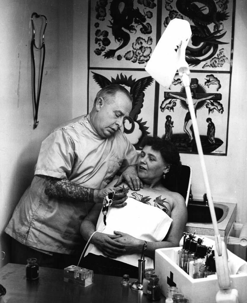 February 1965: A tattooist painting a bluebird on a woman's breast.   (Photo by Jim Ryan/Keystone Features/Getty Images)