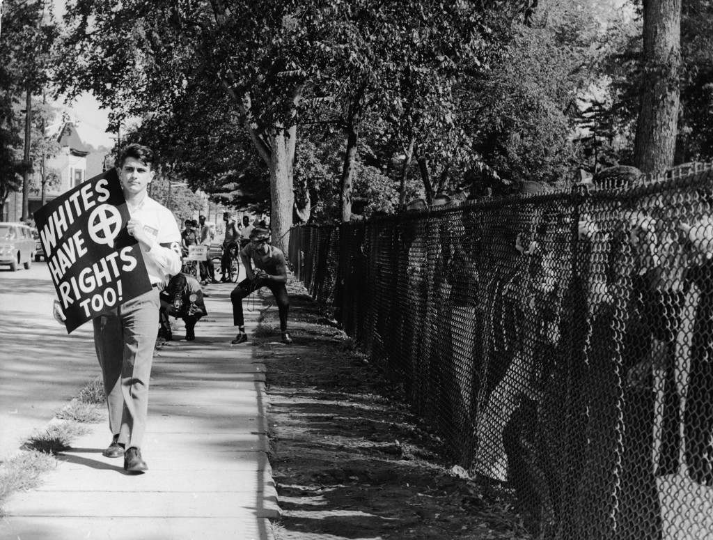 Neo-Nazi John Patler marches on his own to protest desegregating schools as a crowd of people watches, Englewood, New Jersey, August 20, 1962. Patler was marched as the founder of the White Shirt American National Party. He was arrested and jailed in 1967 for the assassination of rival George Lincoln Rockwell, leader of the American Nazi Party. (Photo by Hulton Archive/Getty Images)