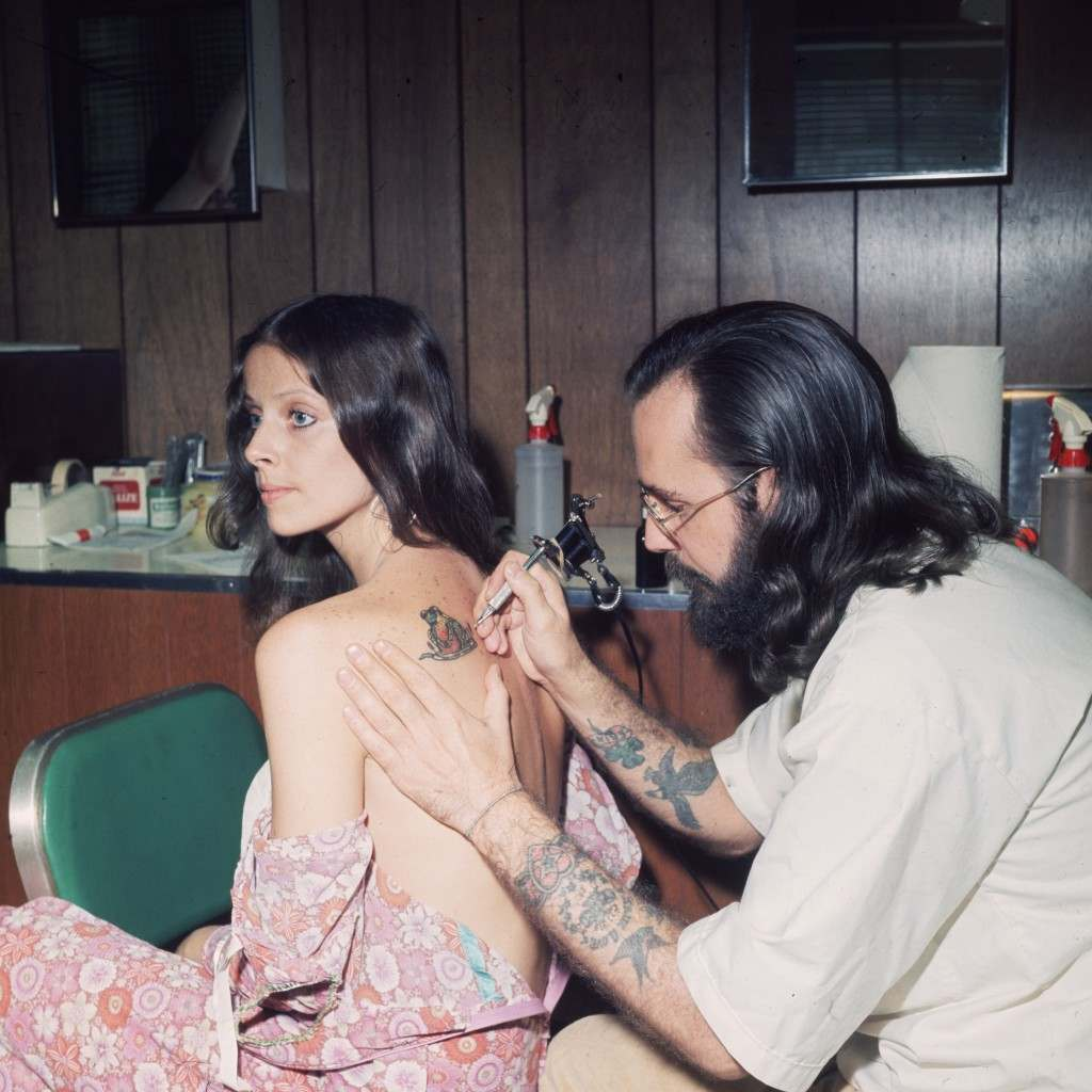 17th August 1973:  An American tattoo artist working on a client's shoulder.  (Photo by F. Roy Kemp/BIPs/Getty Images)