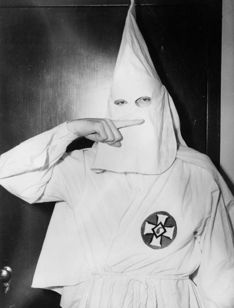February 1947:  Stetson Kennedy, author of the Ku Klux Klan study 'Southern Exposure', posing in the Klan's uniform to illustrate the sign of the cross made before the altar at KKK meetings.  (Photo by Keystone Features/Getty Images)
