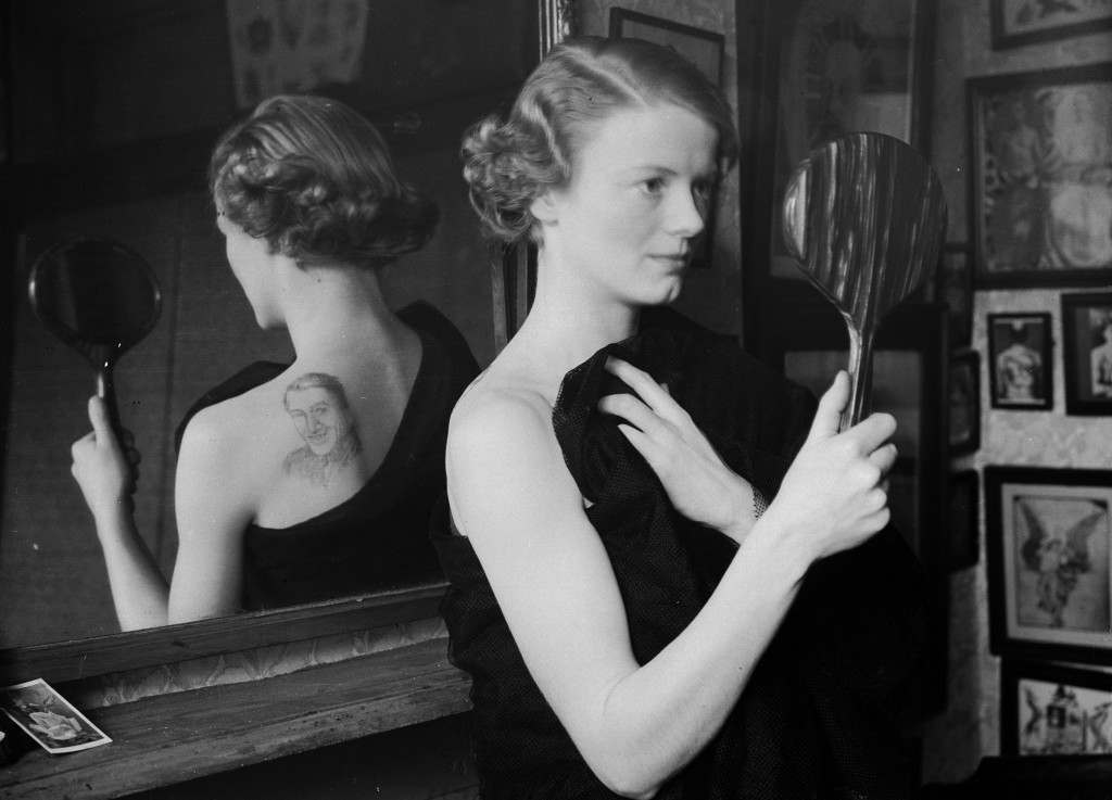 14th November 1936:  A film fan uses a mirror to admire the image of film star Gary Gooper she has had tattooed on her back by George Burchett a London tattooist.  (Photo by William Vanderson/Fox Photos/Getty Images)