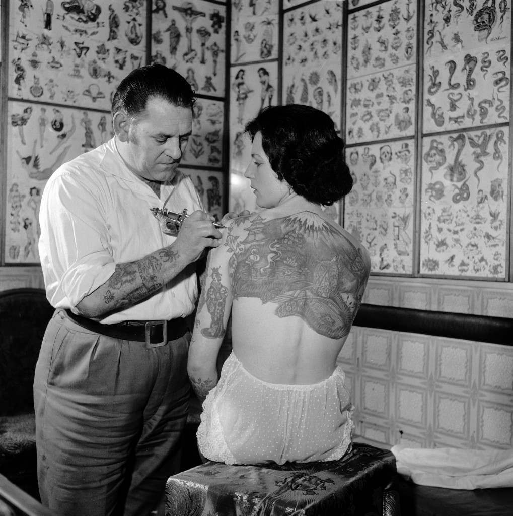 April 1960:  Tattooist Les Skuse at work on champion tattoo lady Pam Nash who has a large Japanese scene across her back.  (Photo by John Pratt/Keystone Features/Getty Images)