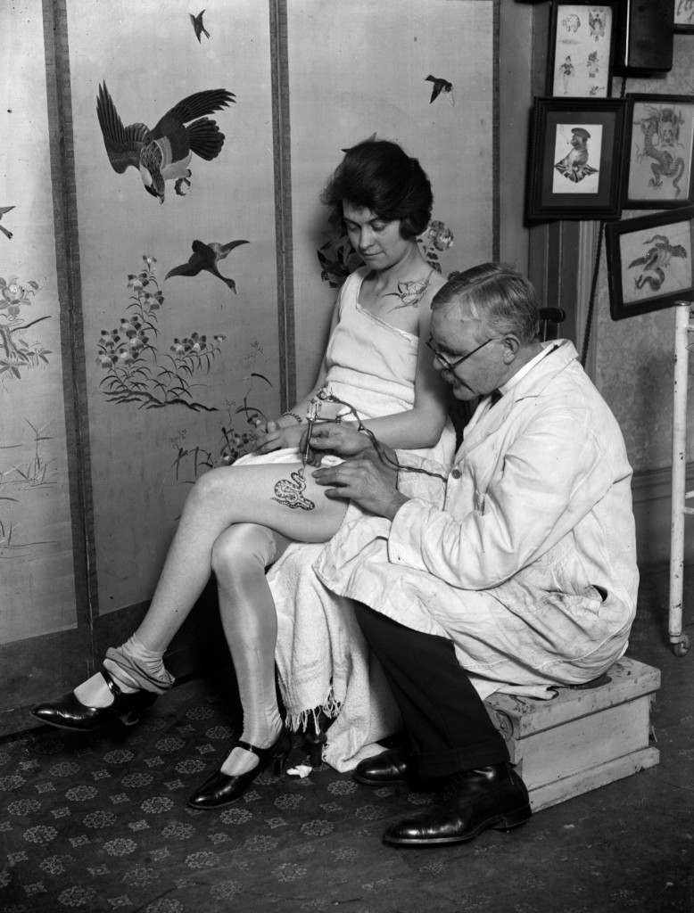 March 1928:  A woman having an image of a snake tattooed onto her thigh by tattooist, George Burchett.  (Photo by Fox Photos/Getty Images)