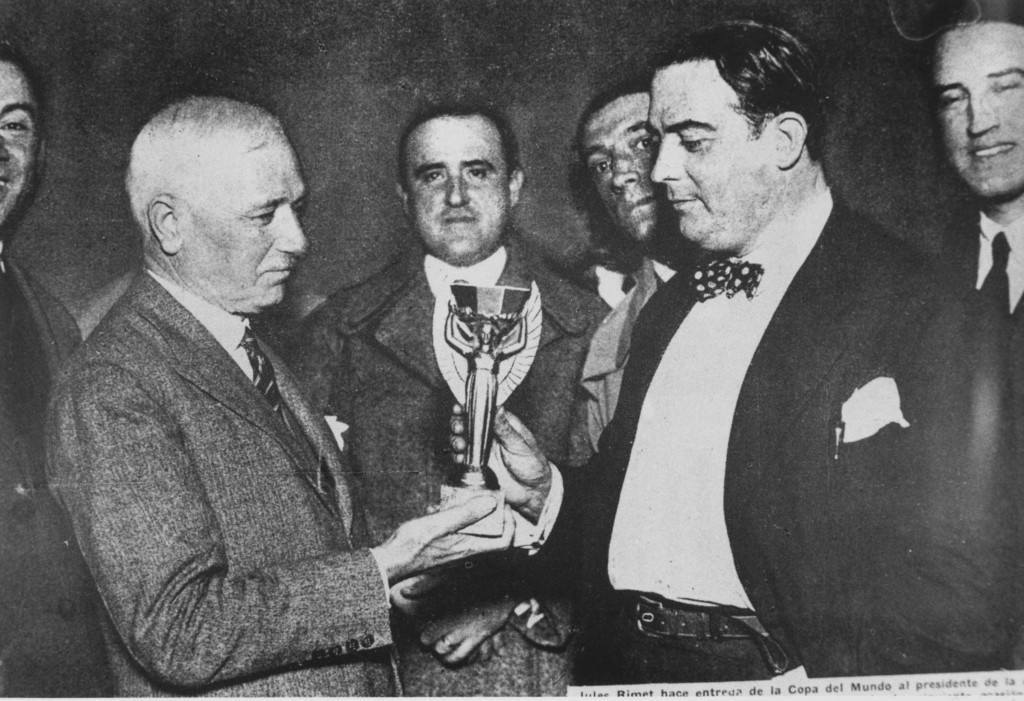30th July 1930:  Jules Rimet, president of FIFA (Federation Internationale de Football), presents the first World Cup trophy (the Jules Rimet Trophy) to Dr Paul Jude, the president of the Uruguayan Football Association, after Uruguay beat Argentina 4-2 in the first ever World Cup final in Montevideo, Uruguay.  (Photo by Keystone/Getty Images)