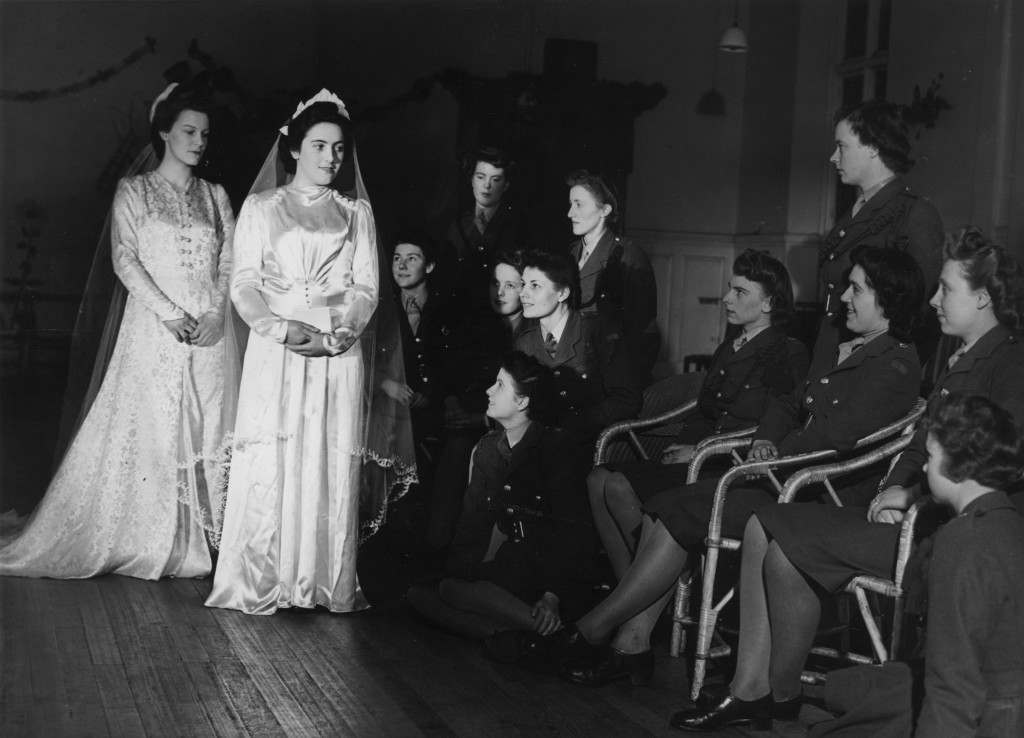 6th January 1944:  ATS girls watch models displaying wedding dresses from a pool set up by the War Office to save ATS girls the expense of buying special wedding wear.  (Photo by Fred Morley/Fox Photos/Getty Images)
