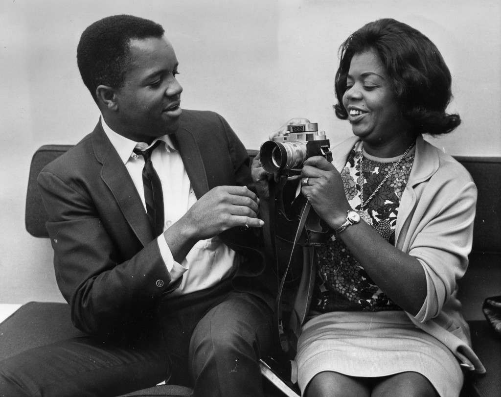 9th October 1964: Berry Gordy Jnr, American songwriter ('Reet Petite'), impresario and founder of the Tamla Mowtown record label, shows his camera to Mrs Edwards. (Photo by Victor Drees/Evening Standard/Getty Images)