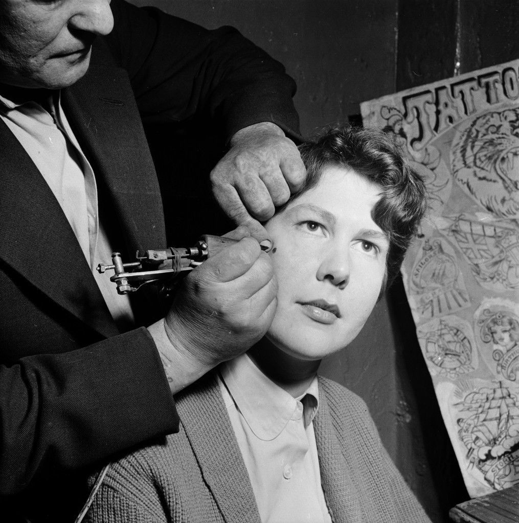 May 1956:  A tattoo artist paints a permanent beauty spot onto the cheek of a female client at his workshop in Copenhagen.  (Photo by John Firth/BIPs/Getty Images)