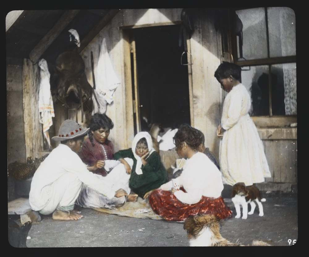 Maori woman and children playing cards on doorstep of home - Whakarewarewa Contributor Names Jackson, William Henry, 1843-1942, photographer