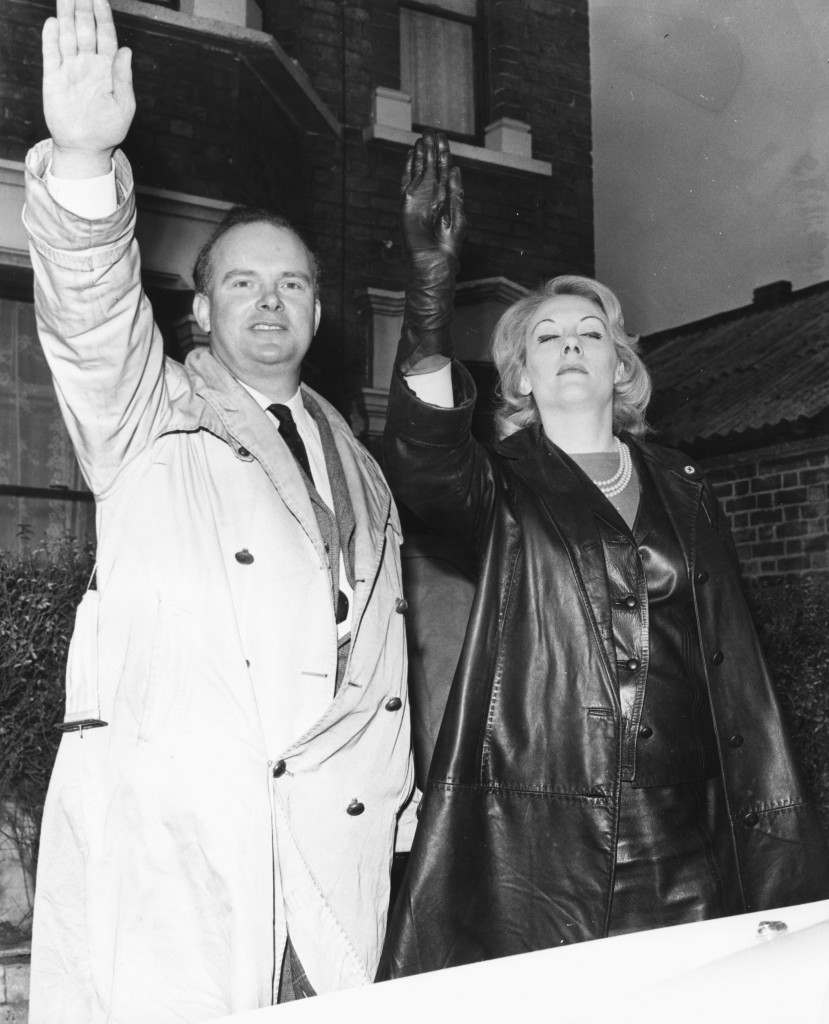 Leader of the Nationalist Socialist Movement Colin Jordan and hid wife, giving the Nazi salute to photographers following his speech at the Town Hall, January 11th 1965. (Photo by Jim Gray/Keystone/Getty Images)