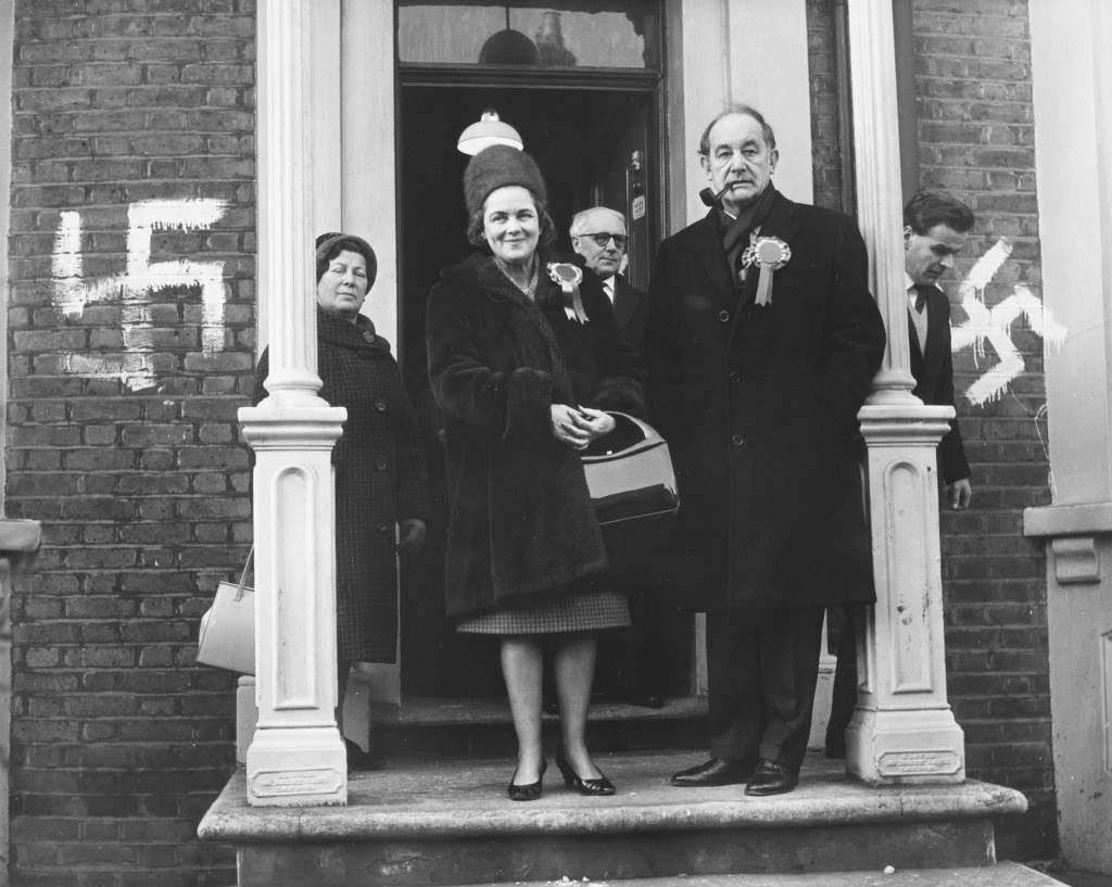 Patrick Gordon Walker, Labour Party candidate and former Foreign Secretary, with his wife leaving the committee rooms, which have been covered by graffiti swastikas, during the by-election campaign, Leyton, London, Janaury 4th 1965. (Photo by Douglas Miller/Keystone/Getty Images)