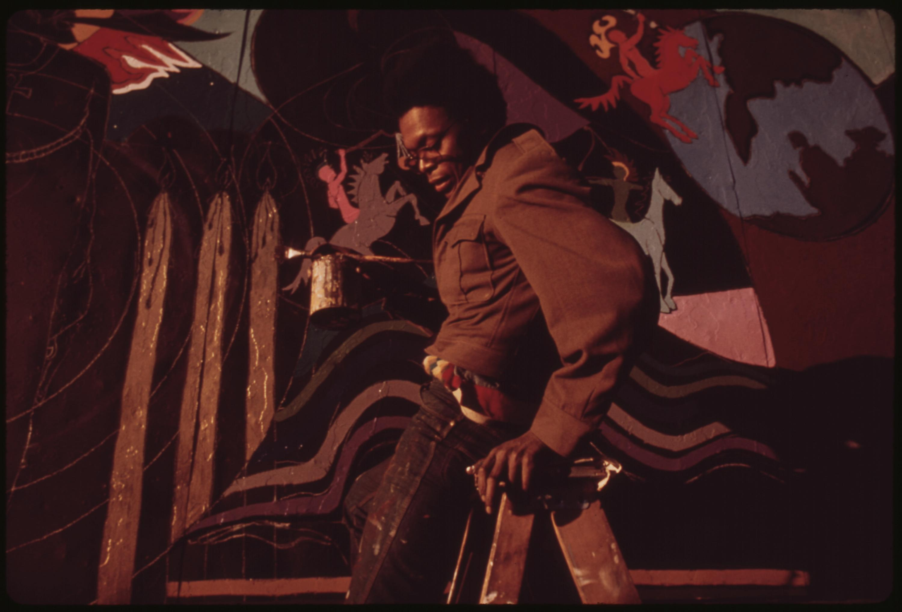 Artist Ron Blackburn Painting An Outdoor Wall Mural At The Corner Of 33rd And Giles Streets In Chicago. He Is One Of Many Artists Painting In The City's Black Communities, 06:1973