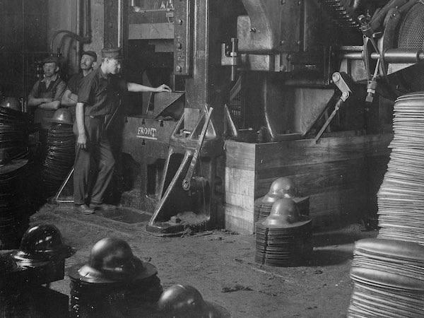 View of workers operating a large power press for shaping helmets, in the plant of Hale & Kilburn Corporation, New York.