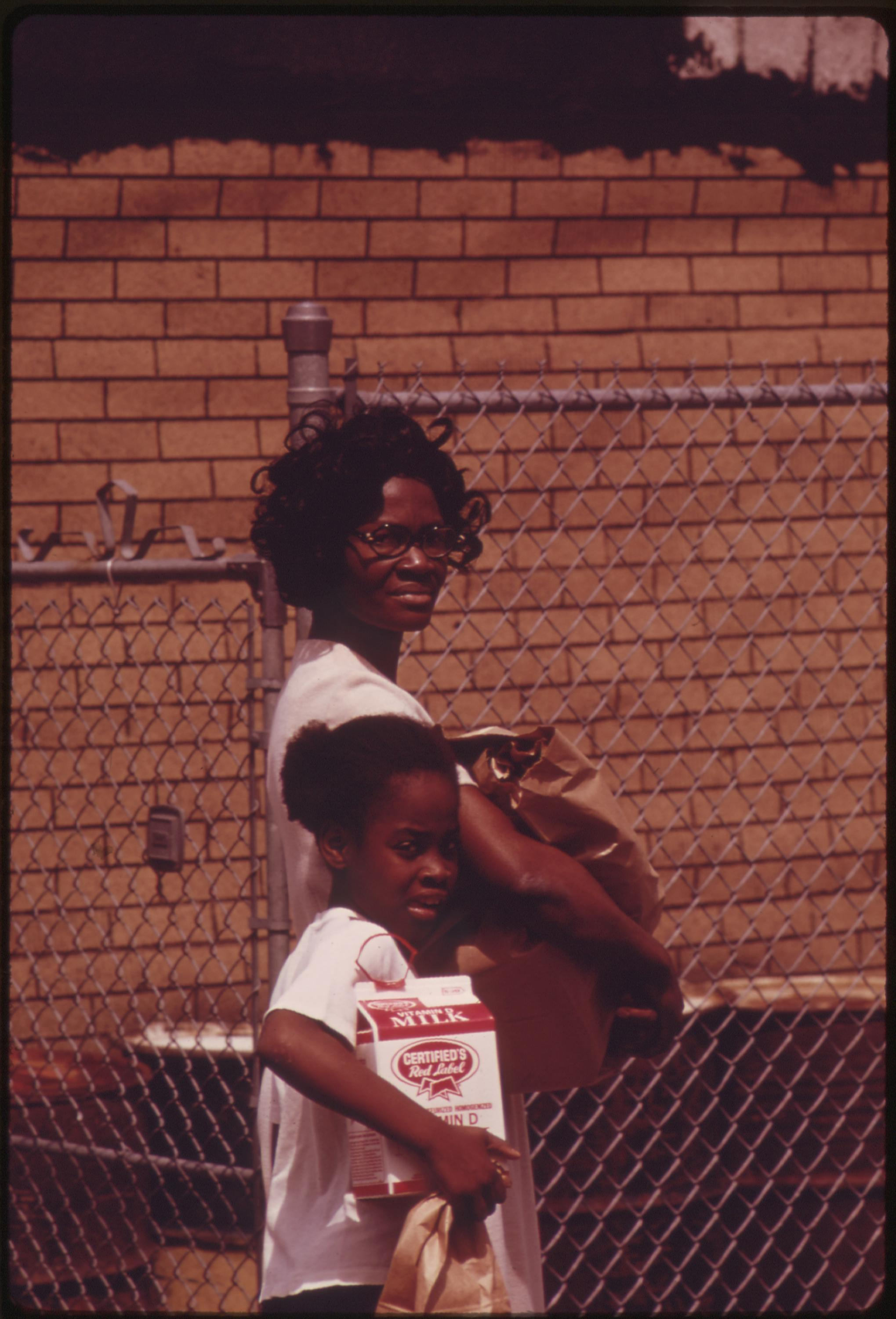 Mother And Daughter Returning Home After A Grocery Shopping Expedition In Chicago's West Side Black Community, 06:1973 John H. White