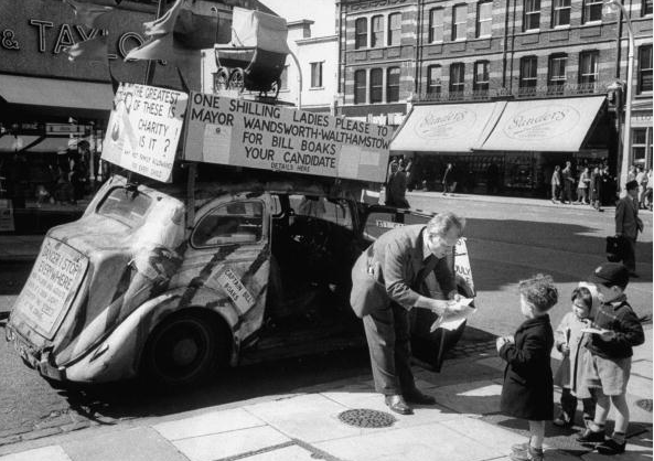 British Captain William Boaks stepping out of the billboard covered car in the street and talking to three little children. (Photo by Brian Seed/The LIFE Images Collection/Getty Images)