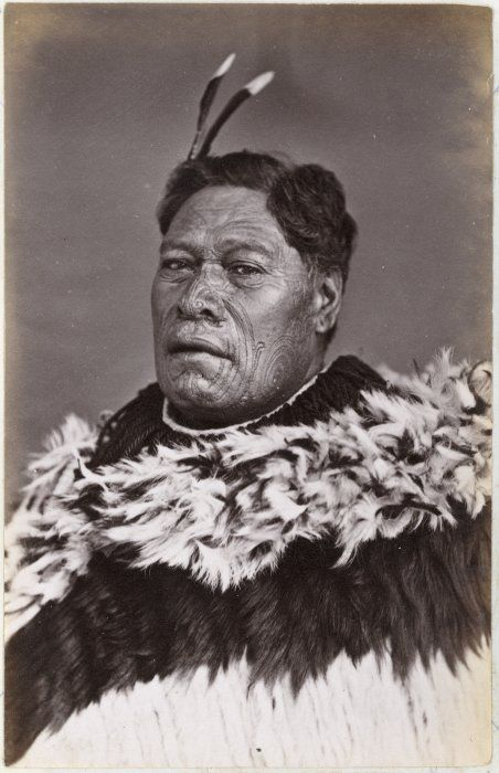 Head and shoulders portrait of Tamati Waka Te Puhi, probably photographed by the Foy Brothers of Thames between 1872-1886. Shows a man with a moko. He wears cloak decorated with feathers. Via