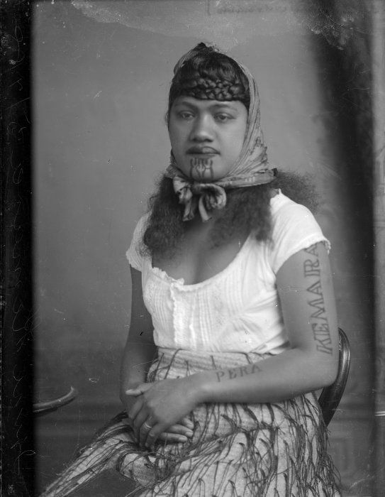 "Carte de visite portrait of Irini Kemara, a young Maori woman with the words ""Pera"" and ""Kemara"" tattooed on her left arm, taken in July 1888 by Samuel Carnell of Napier. She is wearing a korowai (tag cloak) around her waist."