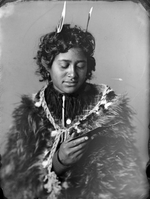 Carte de visite portrait of Ruruhira, a Maori woman from the Hawkes Bay district, taken, probably in the 1890s, by Samuel Carnell of Napier. She is looking at a cabinet card photograph common in that decade.