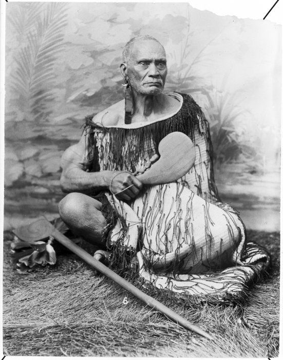 "Take Take Rangitupu from Ranana, Wanganui River, ca 1880s Reference Number: 1/2-020056-F Seated studio portrait of Take Take Rangitupu from Ranana, Wanganui River. He wears an ear adornments made of ribbon and an animal tooth. He wears a korowai (Maori tag cloak) and holds a patu. A tewhatewha lies at his feet. He sits before a painted backdrop. Photograph taken circa 1880s. Photographer unidentified. Key terms: 1 image, related to d ca Take Take Rangitupu, Patu, Tewhatewha, Rangatira, Korowai, Men, Maori and Maori - Clothing. Part of: Take Take Rangitupu from Ranana, Wanganui River, Reference Number 1/2-020056-F (1 digitised items) Extent: 1 b&w copy negative(s)Film negative. Vertical imageSingle negative Historical Notes: Note on back of print reads: ""Taketake from Tawhitinui and Hiruharama"" Conditions governing access to original: Not restricted Other copies available: File print available in Turnbull Library Pictures920. Taketake, Rangitupu(PFP-026665) Usage: You can search, browse, print and download items from this website for research and personal study. You are welcome to reproduce the above image(s) on your blog or another website, but please maintain the integrity of the image (i.e. don't crop, recolour or overprint it), reproduce the image's caption information and link back to here (http://mp.natlib.govt.nz/detail/?id=32290)"
