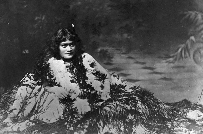 "Princess Te Kirihaehae Te Puea Herangi as a girl, late 1890s Reference Number: 1/2-005159-G Princess Te Kirihaehae Te Puea Herangi as a girl in the late 1890s. She is draped with Kahu huruhuru (Maori feather cloaks). There is a message in Maori across the bottom right hand corner. Photographer unidentified. Key terms: 1 image, categorised under Portraits, related to Princess Te Kirihaehae Te Puea Herangi, Kahu huruhuru and Girls, Maori. Part of: Princess Te Kirihaehae Te Puea Herangi as a girl, Reference Number 1/2-005159-G (1 digitised items) Extent: 1 b&w original negative(s)Film negative. Single negative Historical Notes: Note on back of file print reads ""Princess Te Puea Herangi, 1884-1952. Photograph taken when she was a girl believed to be dying from tuberculosis."" Conditions governing access to original: Not restricted Usage: You can search, browse, print and download items from this website for research and personal study. You are welcome to reproduce the above image(s) on your blog or another website, but please maintain the integrity of the image (i.e. don't crop, recolour or overprint it), reproduce the image's caption information and link back to here (http://mp.natlib.govt.nz/detail/?id=25267)."