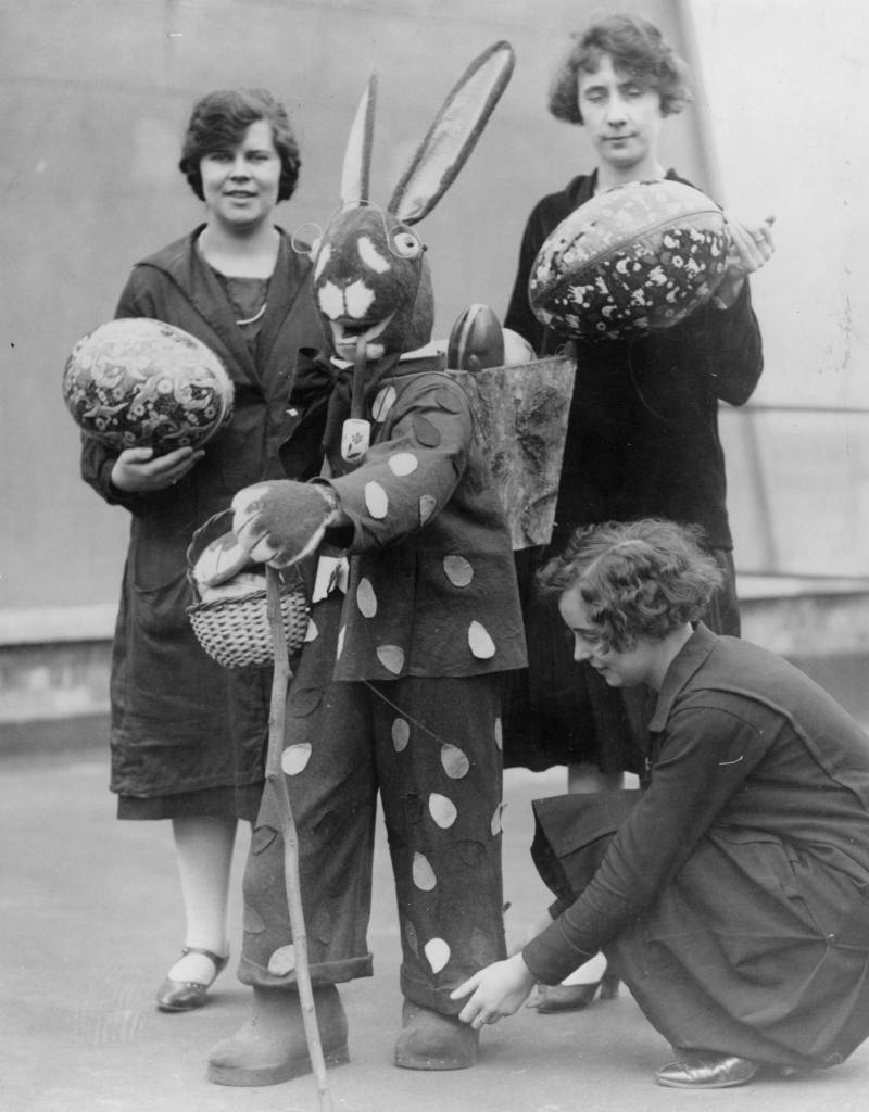 circa 1930: An Easter bunny carries easter eggs in a basket on his back while one woman adjusts his turn-ups and two others carry large easter eggs. (Photo by General Photographic Agency/Getty Images)
