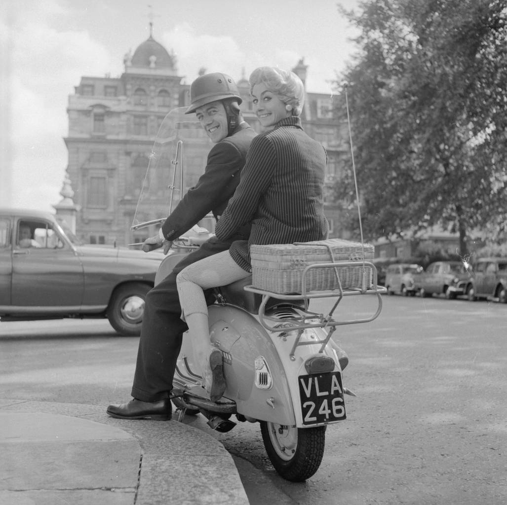 August 1958:  Scooter riders Ron Edney of London and his girlfriend Jean Keyser. Jean is wearing a wig with a specially strengthened base designed by London hairdresser Raymond with the fashion conscious female motorcyclist in mind.  (Photo by Ken Harding/BIPs/Getty Images)